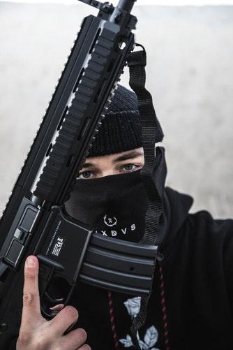 Un homme cagoulé avec une arme en main