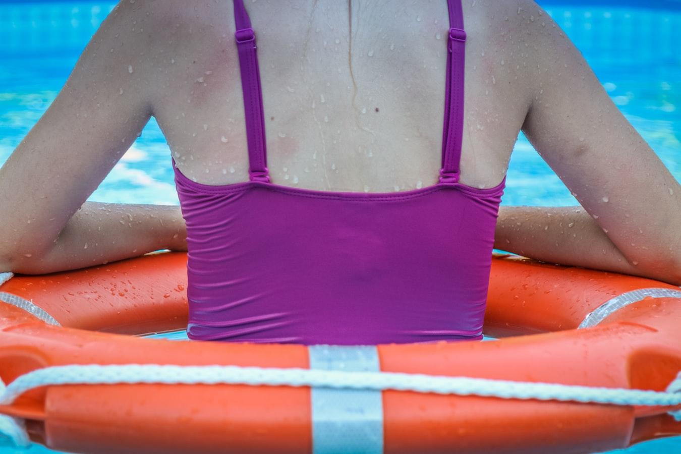 Une jeune fille avec un canot de sauvetage dans une piscine