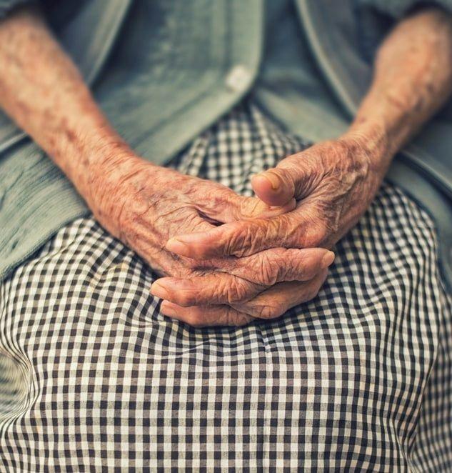 Une vieille femme indienne assise avec les mains croisés sur les genoux