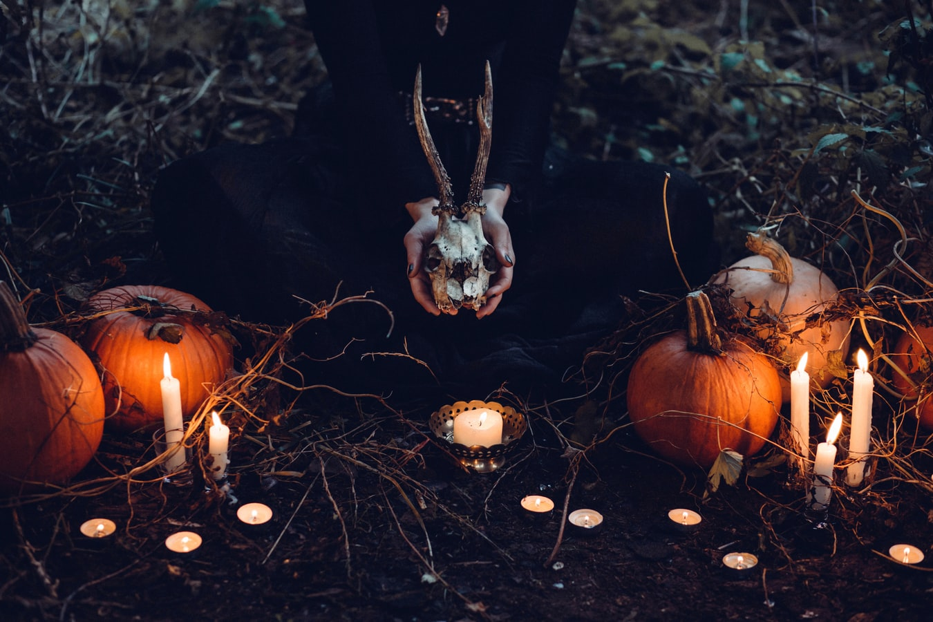 Une sorcière célébrant Halloween avec citrouilles et bougies dans une forêt