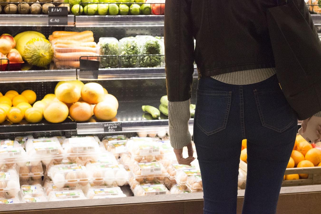 Une femme devant un rayon de fruits et légumes.