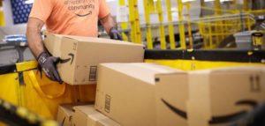 Un employé soulevant des cartons dans un entrepôt d'Amazon.