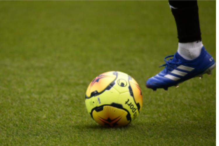 Le pied d'un footballeur devant une balle.